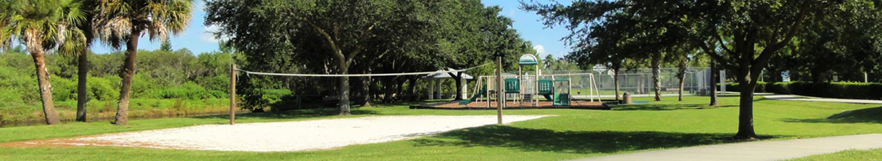 Sand volleyball court and playground at park